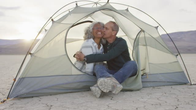 Senior adult couple embracing and kissing in a tent