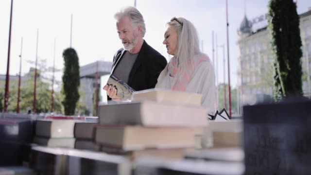 senior adult couple on holiday looking at books on flea market - mercato delle pulci video stock e b–roll