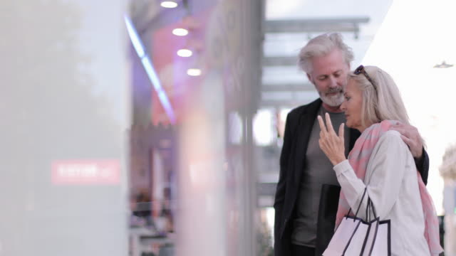 senior adult couple on holiday looking at shop window - schaufenster stock-videos und b-roll-filmmaterial
