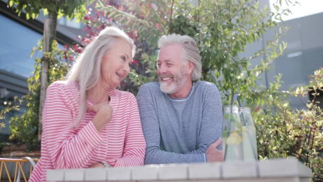 vídeos y material grabado en eventos de stock de senior adult couple sitting on outdoors terrace drinking in sunshine - terraza