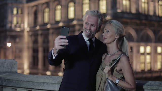 senior adult couple taking selfie in front of opera on evening out - 歌劇点の映像素材/bロール