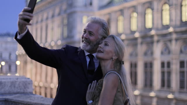 senior adult couple taking selfie in front of opera on evening out - evening gown stock videos & royalty-free footage