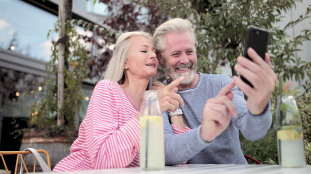 senior adult couple video call friends on holiday - pensionierung stock-videos und b-roll-filmmaterial