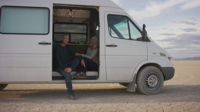 senior adult couple visiting in doorway of their campervan - pacific islander couple stock videos & royalty-free footage