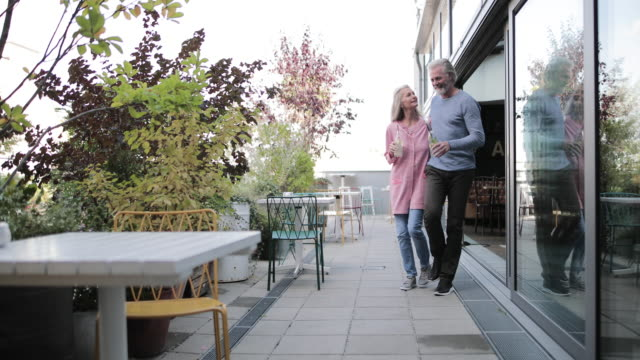 senior adult couple walking to table at luxury hotel - vollbart stock-videos und b-roll-filmmaterial
