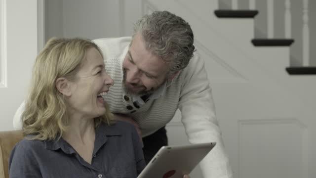vídeos de stock e filmes b-roll de senior adult couple working from home on laptop - caucasian ethnicity
