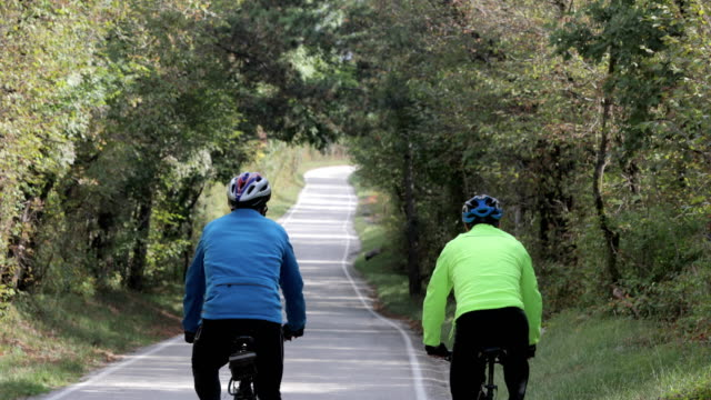 senior adult cycling friends on the move on country road - side by side stock videos & royalty-free footage