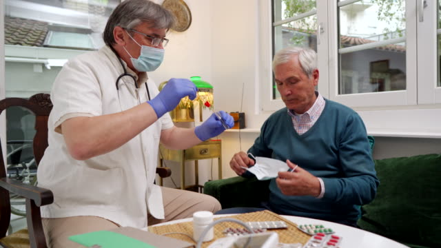 senior adult doctor taking a mouth sample from an ill patient - prescription medicine home stock videos & royalty-free footage