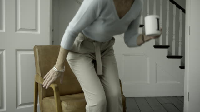 senior adult female relaxing at home - mug video stock e b–roll