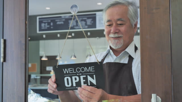 senior adult hand flip the sign to open the shop, come in we're open, vintage black retro sign. - apron stock videos & royalty-free footage