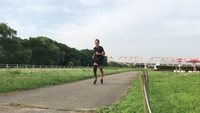 義肢を身に着けているシニア大人のジョギング - ジョギング点の映像素材/bロール