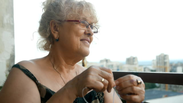 vidéos et rushes de senior dame adulte tricot sur un balcon de ville - balcon