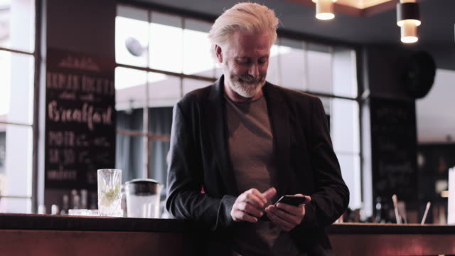senior adult male business man waiting at bar using smart phone - jacket stock videos & royalty-free footage