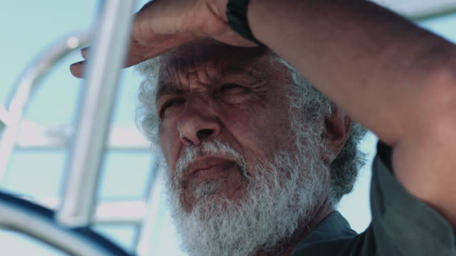 Senior adult male captain looking out on sailboat