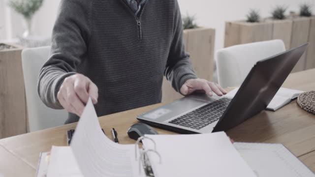 vidéos et rushes de senior adult male doing domestic finance on laptop at kitchen table, day in life - seniornaute