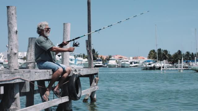vídeos y material grabado en eventos de stock de senior adult male fishing on pier - mérida méxico