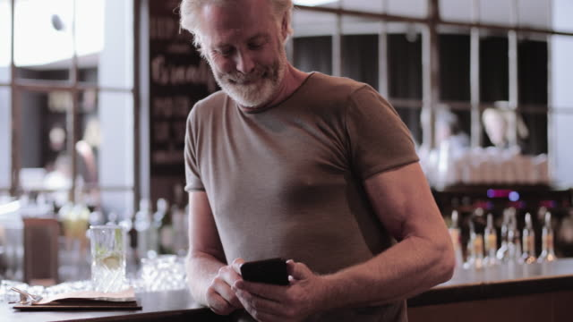 vidéos et rushes de senior adult male waiting at bar in hotel lobby looking at smart phone - hall d'accueil