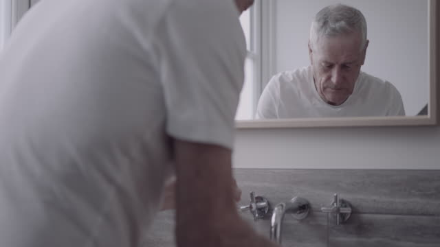 senior adult male washing face in bathroom in the morning and looking in mirror - in front of stock videos & royalty-free footage