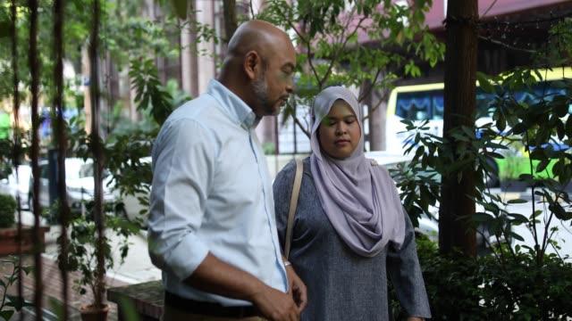 senior adult man consoling a malaysian woman - sad old asian man stock videos & royalty-free footage