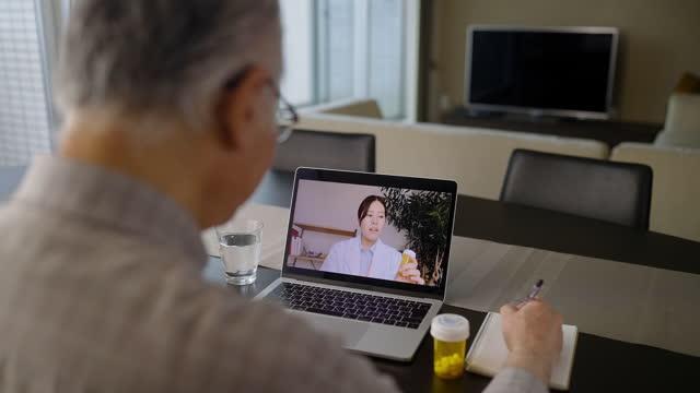 vídeos de stock, filmes e b-roll de idoso adulto tendo reunião remota de telemedicina por chamada de vídeo em laptop com médica em sala de estar em casa - exame médico procedimento médico