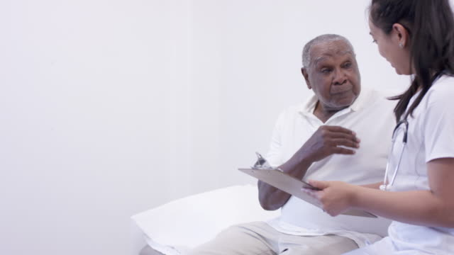 senior adult man in consultation with female doctor - note pad stock videos & royalty-free footage