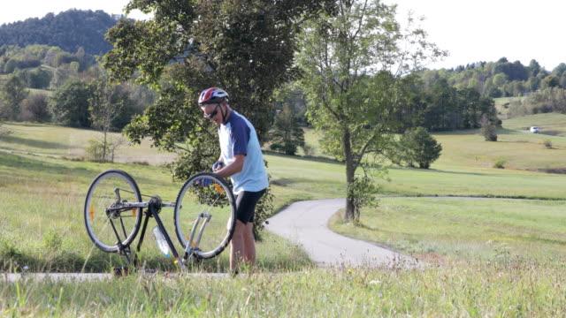 stockvideo's en b-roll-footage met senior volwassen man het opblazen van de platte band op de fiets op landweg - autoband