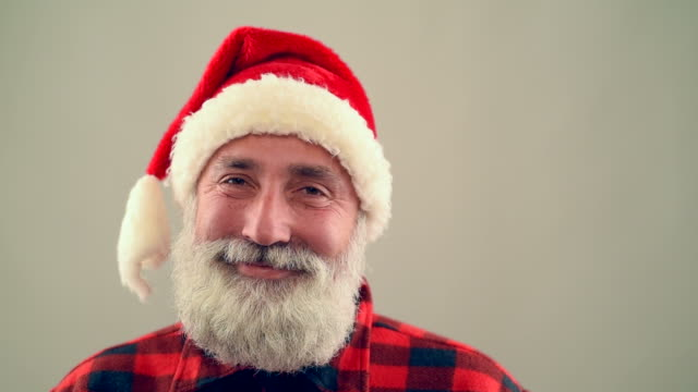 senior adult man looking into the camera and smiling santa claus hat on a gray background. slow motion - santa hat stock videos & royalty-free footage