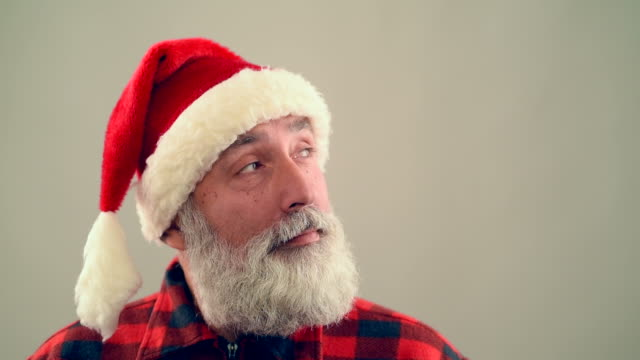 senior adult man nods his head and smiling santa claus hat on a gray background. - santa hat stock videos & royalty-free footage