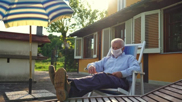 senior adult man reading a book during the lockdown at home - outdoor chair stock videos & royalty-free footage