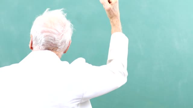 Senior adult man scientist, mathematician wearing lab coat with chalkboard.