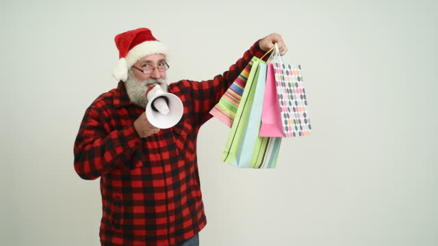 senior adult man showing copy space and presents in santa claus hat on a gray background - santa hat stock videos & royalty-free footage