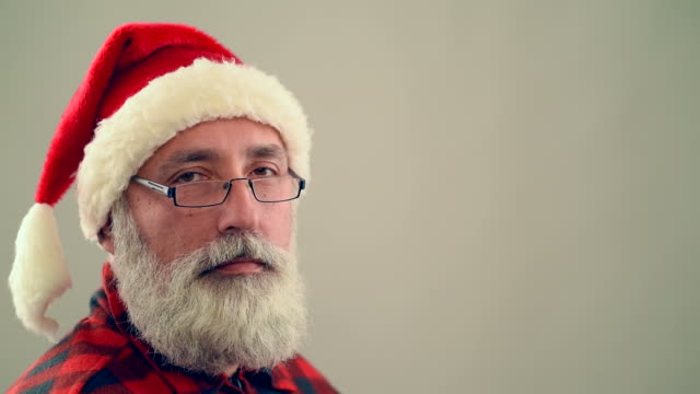 senior adult man winking and smiling santa claus hat on a gray background. - santa hat stock videos & royalty-free footage
