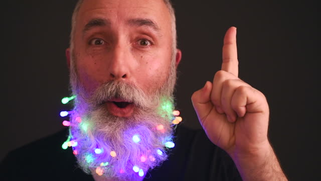 senior adult man with a beard decorated with christmas garlands is an idea - t shirt stock videos & royalty-free footage