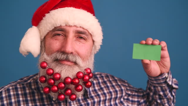 senior adult man with a beard in elegant hat of santa claus on a blue background - plaid shirt stock videos & royalty-free footage