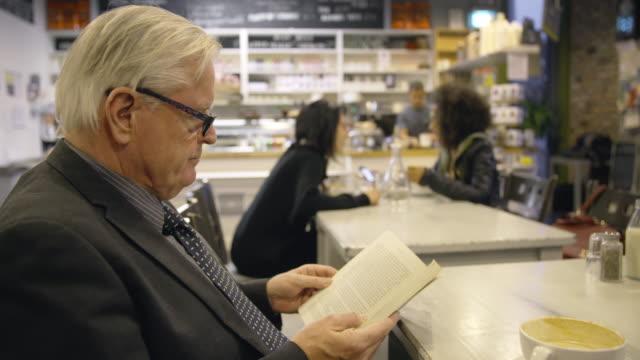 vídeos de stock, filmes e b-roll de senior adulto lendo livro em um café - óculos de leitura