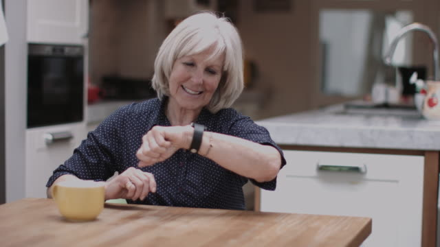 Senior Adult using smart watch at home on kitchen table