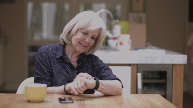 vídeos de stock e filmes b-roll de senior adult using smart watch at home on kitchen table - computador utilizável como acessório