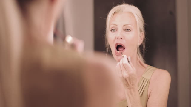 senior adult woman applying make up in mirror and getting dressed - mirror stock videos & royalty-free footage
