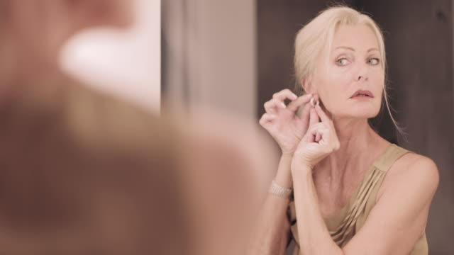 senior adult woman applying make up in mirror and getting dressed - orecchini video stock e b–roll