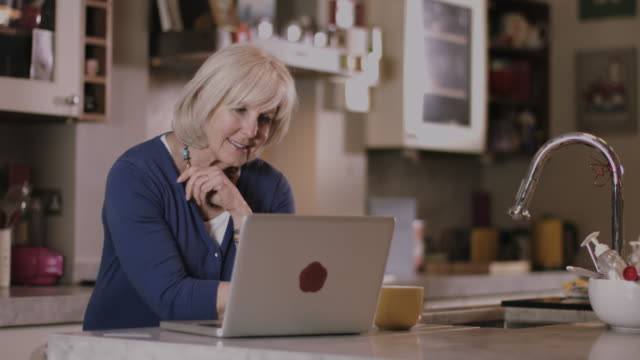 stockvideo's en b-roll-footage met senior adult woman at home shopping online - oudere internetgebruiker