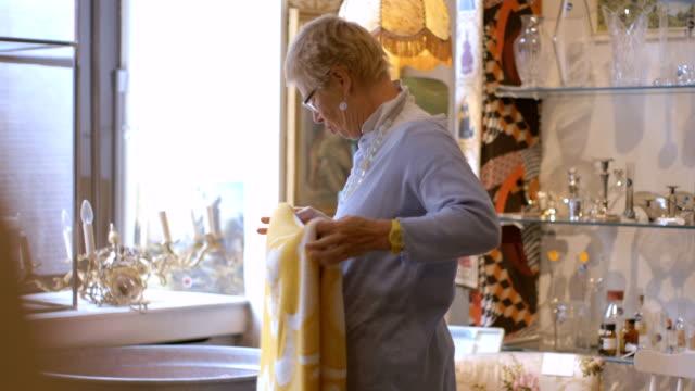 vidéos et rushes de senior adulte femme navigation dans un magasin d'antiquités - miroir ancien