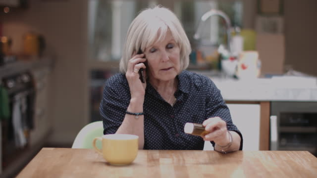 senior adult woman calling doctor and holding medicine at home - prescription medicine home stock videos & royalty-free footage