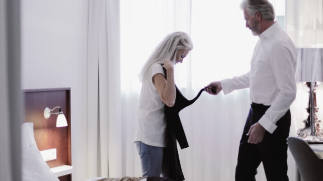 senior adult woman choosing dress to wear - elegante kleidung stock-videos und b-roll-filmmaterial