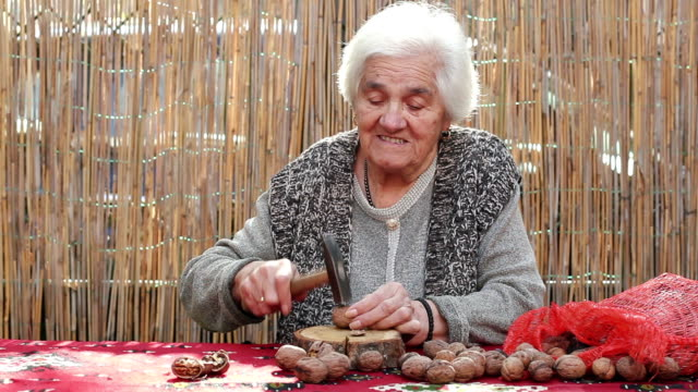 senior adult woman cracking walnut with hammer