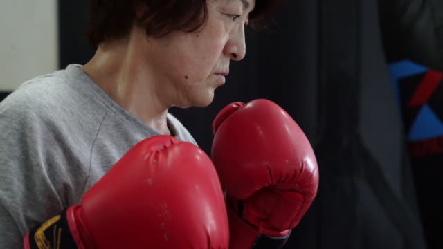 senior adult woman hitting sandbag - senior women stock videos and b-roll footage