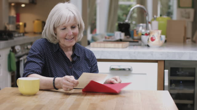senior adult woman opening valentine's day card at kitchen table - greeting card stock videos & royalty-free footage