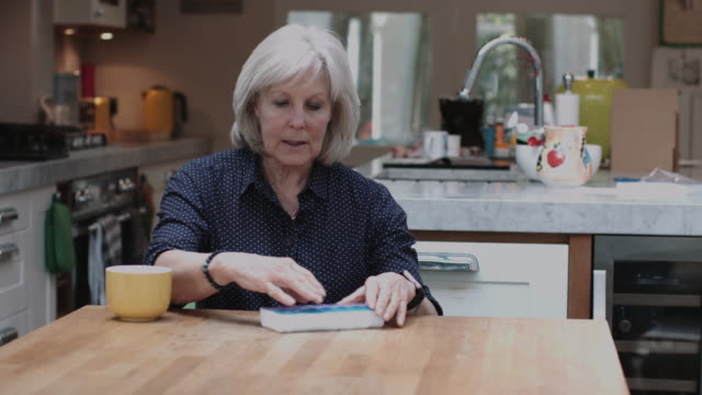 Senior Adult woman taking medicine at home in kitchen
