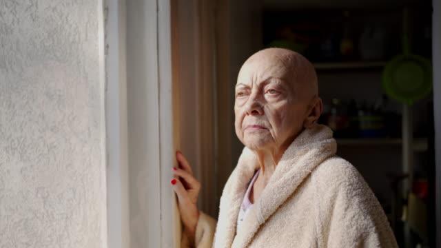 癌と脱毛を持つシニアアダルト女性、窓から見て - 髪の毛のない頭点の映像素材/bロール