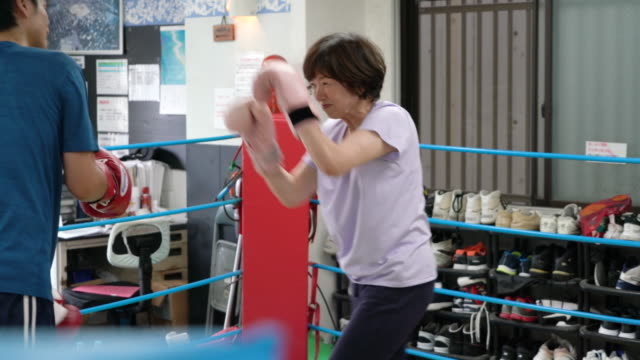 vídeos de stock e filmes b-roll de senior adult women boxercise training with mid adult coach - sports training