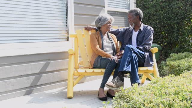シニア アフリカ系アメリカ人カップルがベンチでおしゃべり - ベンチ点の映像素材/bロール